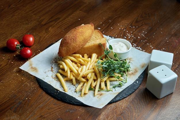 Paniertes hähnchenschnitzel, gefüllt mit butter, frittiert mit einer beilage aus pommes frites. traditionelles urkain-gericht - kiewer schnitzel. nahaufnahme auf leckeres essen