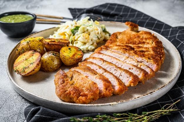 Paniertes wiener schnitzel mit ofenkartoffeln und salat. grauer hintergrund. draufsicht