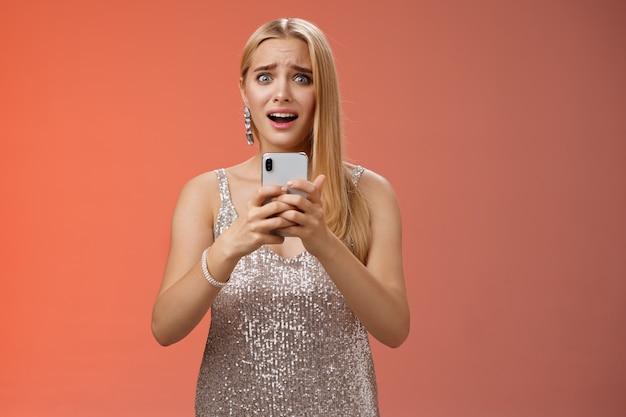 Panik schockierte frau besorgt fotos durchgesickert internet-look angst ängstlich große augen kriechen besorgt halten smartphone schüttelte sprachlos keuchend verängstigte freunde finden geheimen, roten hintergrund.