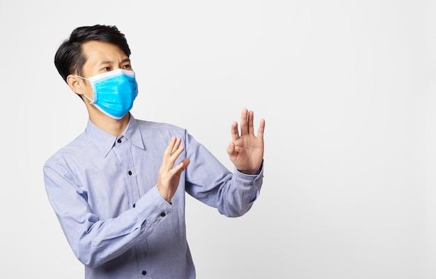 Panikstörung des asiatischen mannes, die chirurgische maske trägt, die mund und bedeckt