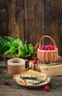 Panini-sandwich mit käse- und senfblättern. morgen kaffee. dorffrühstück