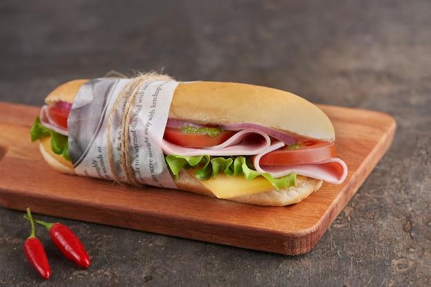 Panini-sandwich mit schinken und käse mit frischen tomaten und salat auf holzbrett.