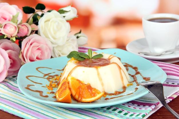 Panna cotta mit orangenschale und karamellsauce, auf farbigem holzhintergrund