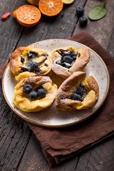 Pannukakku oder dänischer pfannkuchen mit beeren, die mit zuckerpulver bedeckt sind