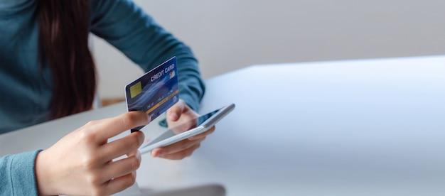 Panorama-banner. junge frau sicherheitscode mit handy smartphone eingeben und bezahlen kreditkarte am schreibtisch zu hause büro