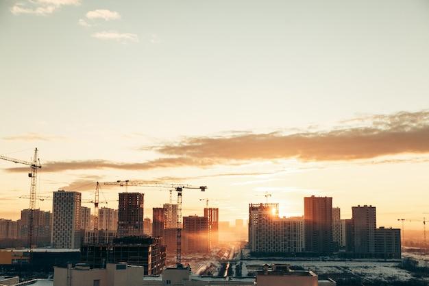 Panorama der konstruktion bei sonnenuntergang. bau einer wohnanlage mit kränen.