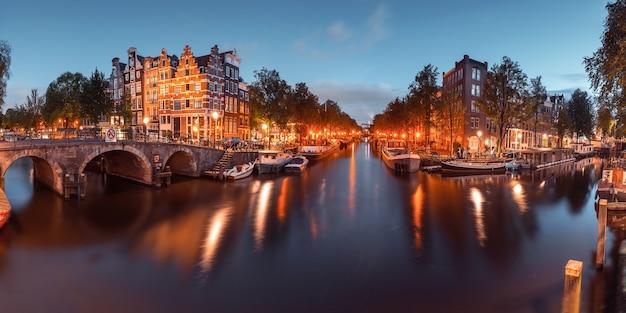 Panorama des amsterdamer kanals, der brücke und der typischen häuser, der boote und der fahrräder während der abenddämmerungsblauen stunde, holland, niederlande. gebrauchtes tonen