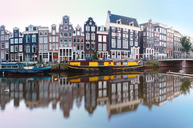 Panorama des amsterdamer kanals singel mit typischen holländischen häusern, brücke und hausbooten während der morgendlichen blauen stunde, holland, niederlande.