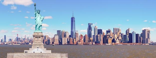 Panorama des freiheitsstatuen mit dem one world trade building center über dem hudson river und dem new york cityscape-hintergrund, marksteine von unterem manhattan new york city.
