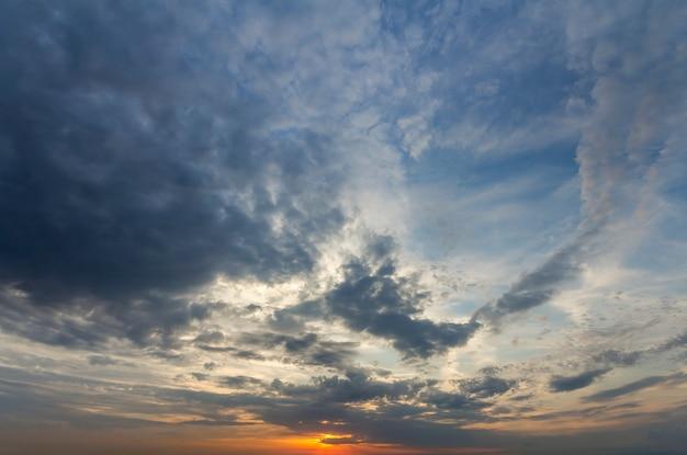 Panorama des himmels bei sonnenaufgang oder sonnenuntergang. schöne ansicht der dunkelblauen wolken beleuchtet durch hellorange gelbe sonne auf klarem himmel. schönheit und kraft der natur, meteorologie und klimawandel.