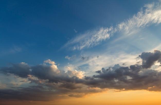 Panorama des himmels bei sonnenaufgang oder sonnenuntergang. schöne ansicht der dunkelblauen wolken beleuchtet durch leuchtend orange gelbe sonne auf klarem himmel. schönheit und kraft der natur, meteorologie und klimawandel.