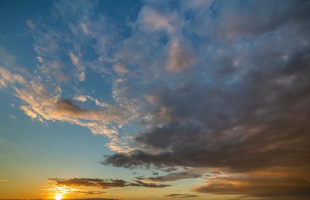 Panorama des himmels bei sonnenaufgang oder sonnenuntergang. schöne ansicht von dunkelblauen wolken beleuchtete durch helle sonne des orange gelbs auf klarem himmel.