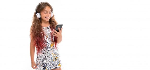 Panorama des mädchens im glitzernden kleid, mit großen weißen kopfhörern, die musik hören und schwarzes smartphone isoliert halten
