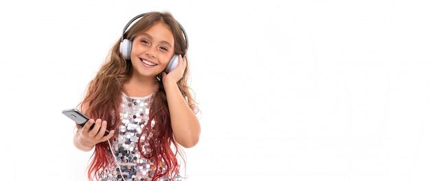 Panorama des mädchens mit großen weißen kopfhörern, die musik hören, ihren linken kopfhörer berühren und schwarzes smartphone isoliert halten