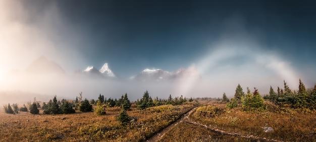 Panorama des nebligen mount assiniboine mit nebelbogenphänomen im herbstwald im provinzpark, alberta, kanada