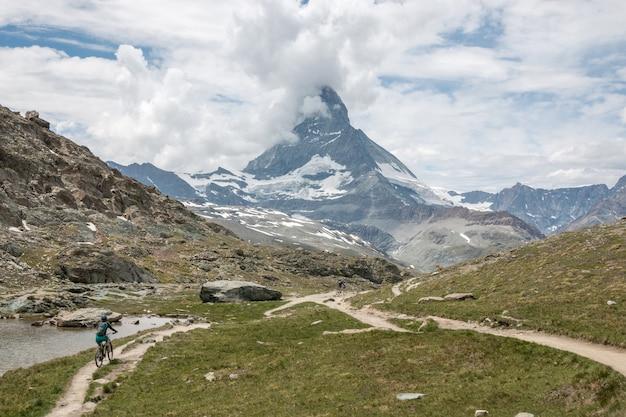 Panorama des riffelsee-sees und des matterhorn-berges, szene im nationalpark zermatt, schweiz, europa. sommerlandschaft, sonnenscheinwetter, dramatischer blauer himmel und sonniger tag