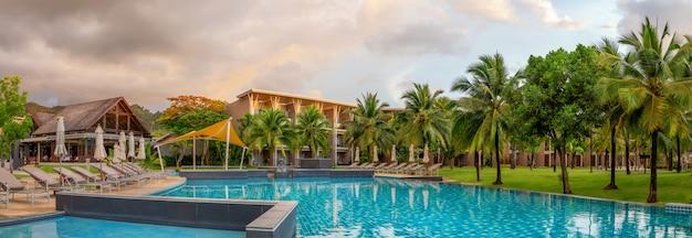 Panorama des schicken fünf-sternehotels mit pool der sand von katathani. abendordnung, palmen und grünes gras. urlaubsort