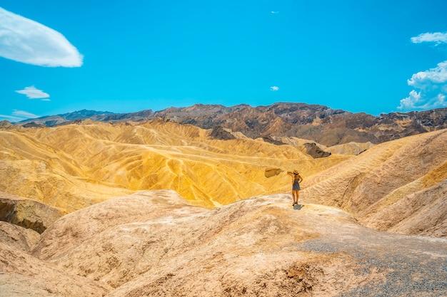 Panorama einer jungen frau im kleid, die den blick auf den aussichtspunkt von zabriskie point, kalifornien genießt. vereinigte staaten