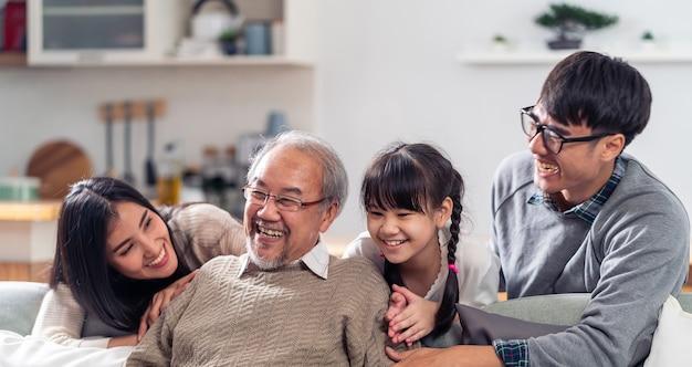 Panorama group portrait der glücklichen asiatischen familie mit mehreren generationen sitzen auf der sofa-couch im wohnzimmer mit einem lächeln.