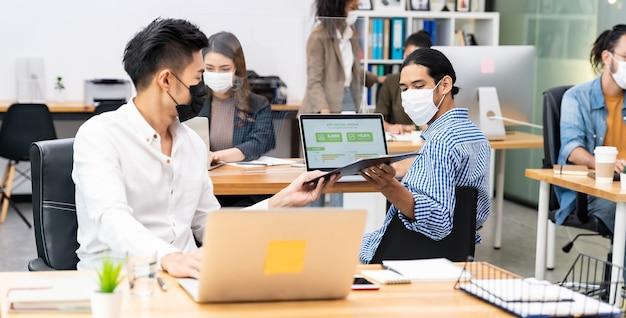 Panorama-gruppe des interracial geschäftsarbeiterteams tragen gesichtsmaske im neuen normalen büro
