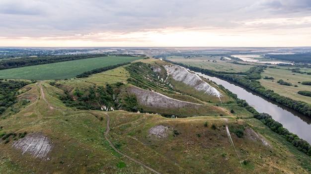 Panorama-luftbild über der spitze einer sommerlandschaft eines grünen landwirtschaftlichen feldes, der hügel oder der berge, eines großen flusses und eines waldgürtels bei sonnenuntergang