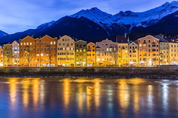 Panorama-nachtansicht von bunten gebäuden und bergen gegenüber dem fluss von innsbruck österreich aus