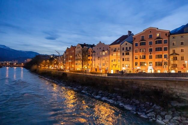 Panorama-nachtblick auf farbenfrohe gebäude gegenüber dem fließenden fluss von innsbruck österreich