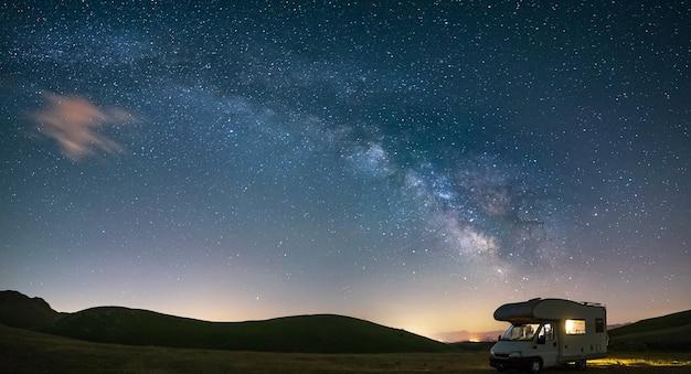 Panorama nachthimmel über campo imperatore hochland, abruzzen, italien. der bogen der milchstraße und die sterne über einem beleuchteten wohnmobil. campingfreiheit in einzigartiger hügellandschaft.