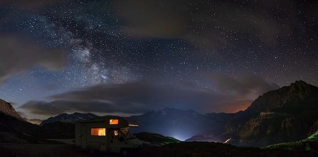 Panorama-nachthimmel über den alpen. der bogen der milchstraße und die sterne über einem beleuchteten wohnmobil. campingfreiheit in einzigartiger landschaft.