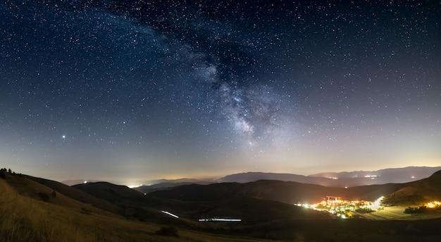 Panorama-nachthimmel über santo stefano di sessanio, abruzzen und rocca calascio, italien. der bogen der milchstraße und die sterne über der beleuchteten einzigartigen hügellandschaft des dorfes. jupiter-planet sichtbar.
