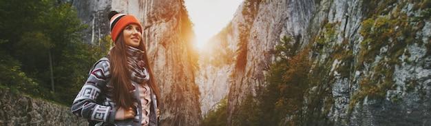 Panorama-porträt des jungen lächelnden mädchens auf hintergrund der sonnigen berge, tragenden orange hut und rucksack.
