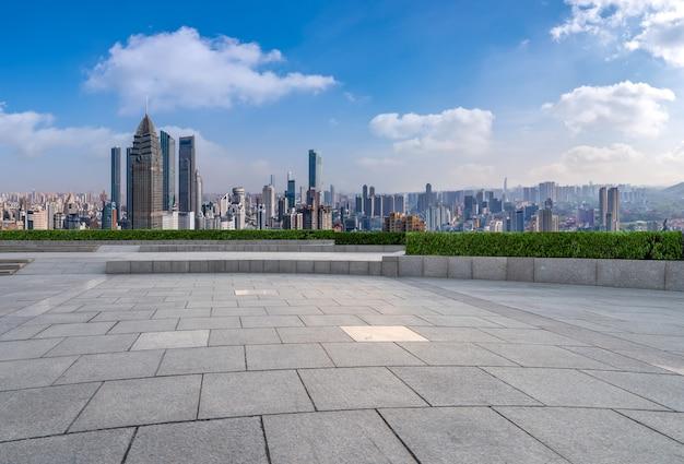 Panorama-skyline und leere quadratische bodenfliesen mit modernen gebäuden