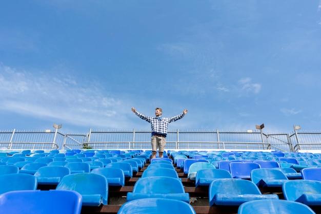 Panorama von enormen stadionsitzen mit einem mann, der die musikereigniskonzerte aufpasst