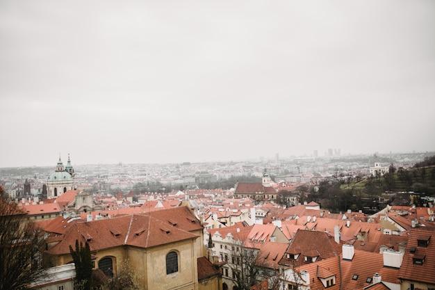 Panorama von prag mit roten dächern und kirche. stadtansicht der altstadt von praha. rustikale graue farbtöne.