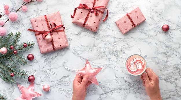 Panorama-weihnachtswohnung lag auf marmortisch. hände halten spielzeugstern und eine tasse cafe latte oder heiße schokolade mit herzform. winterdekorationen: tannenzweige, sterne und rosa schmuckstücke, kopierraum