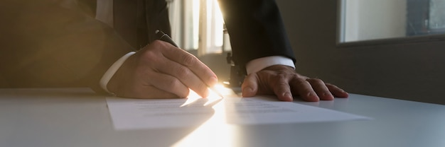 Panoramaansicht des geschäftsmannes in einem schattenbüro, das vertrag unterzeichnet