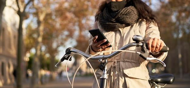 Panoramaaufnahme der hände einer frau, die ihr fahrrad mit ihrem smartphone fährt. sie trägt winterkleidung und ist in einer stadt mit herbstwetter.