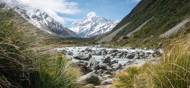 Panoramaaufnahme des gletscherflusses, der an einem sonnigen tag in neuseeland zum berg im hintergrund führt