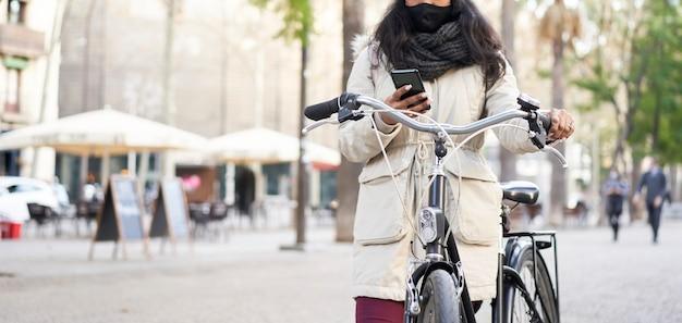 Panoramaaufnahme einer nicht wiedererkennbaren jungen afroamerikanischen frau, die ein smartphone auf ihrem fahrrad benutzt. sie ist in einer stadt.