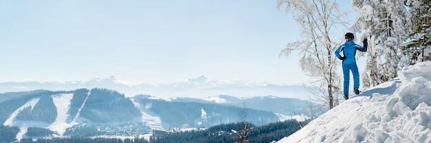 Panoramaaufnahme einer skifahrerin, die oben auf dem berg ruht und natur am skigebiet beobachtet