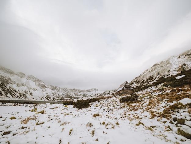 Panoramaaufnahme einer winterlandschaft mit einer kleinen hütte am tatragebirge in polen