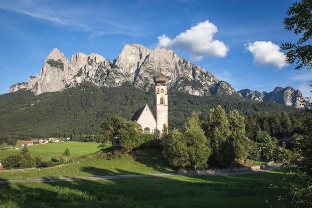 Panoramaaufnahme eines der st. valentin kirche mit dem schlern berg in italien