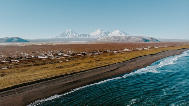 Panoramaaufnahme eines schönen feldes mit dem meer an der seite und erstaunlichen bergen