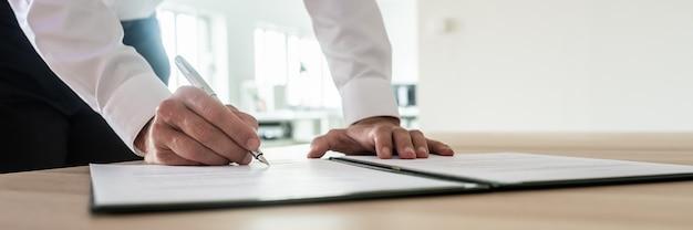 Panoramabild des geschäftsmannes, der wichtiges dokument oder vertrag unterschreibt, während er an seinem schreibtisch steht.