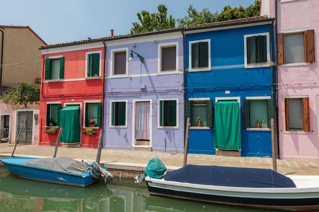 Panoramablick auf bunte häuser und wasserkanal mit booten in burano, einer insel in der lagune von venedig. sonniger sommertag und blauer himmel