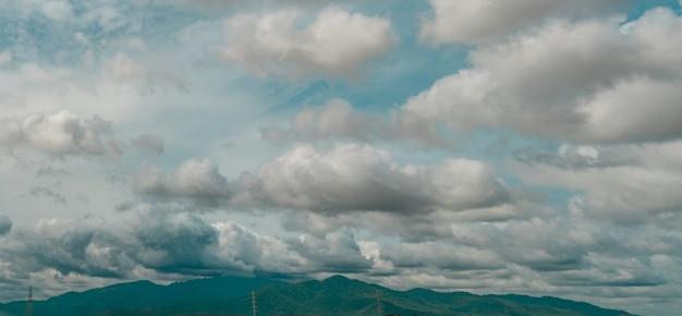 Panoramablick auf den bewölkten himmel über dem grünen berg- und strommastenhimmel und kumuluswolken