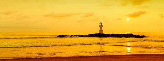 Panoramablick auf den leuchtturm auf einer kleinen felseninsel mit orangefarbenem himmel und dramatischen wolken bei sonnenuntergang. aufgenommen im süden von thailand.