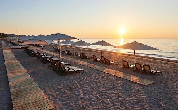 Panoramablick auf den sandstrand am strand mit sonnenliegen und sonnenschirmen gegen meer und berge. hotel. resort. tekirova-kemer. truthahn