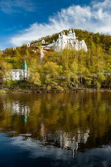 Panoramablick auf den tempel und das orthodoxe kloster auf einem mit laubbäumen bewachsenen hügel