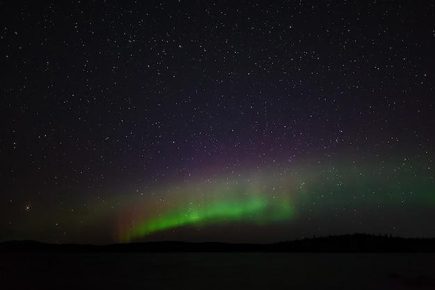 Panoramablick auf die aurora borealis. polarlichter am nächtlichen sternenhimmel über dem see.